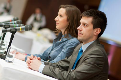 Animateur et animatrice devant des micros lors d'une conférence