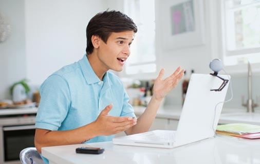 Jeune homme parle à une webcam