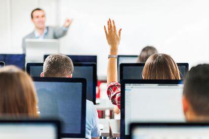 Femme levant la main dans une classe