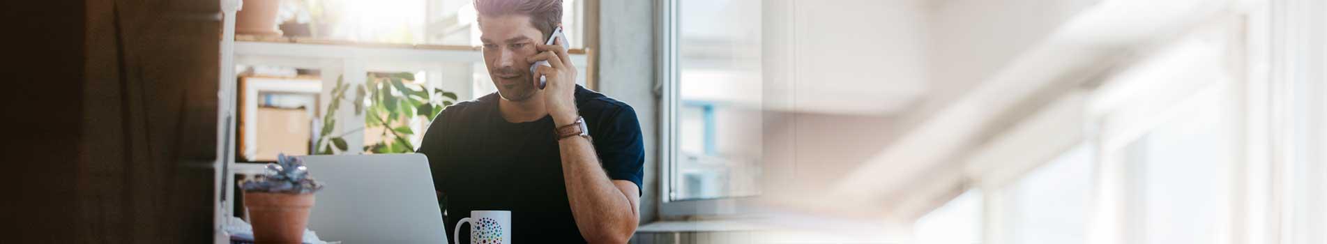 Homme au téléphone devant son ordinateur
