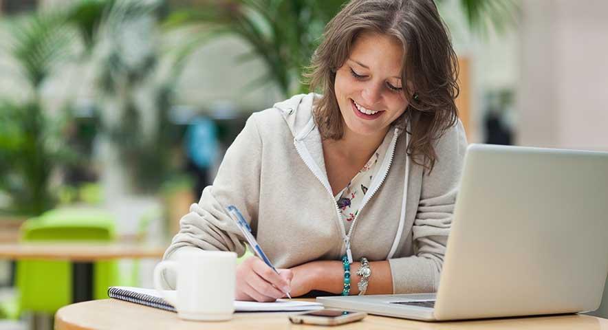 Étudiante souriante devant un ordinateur