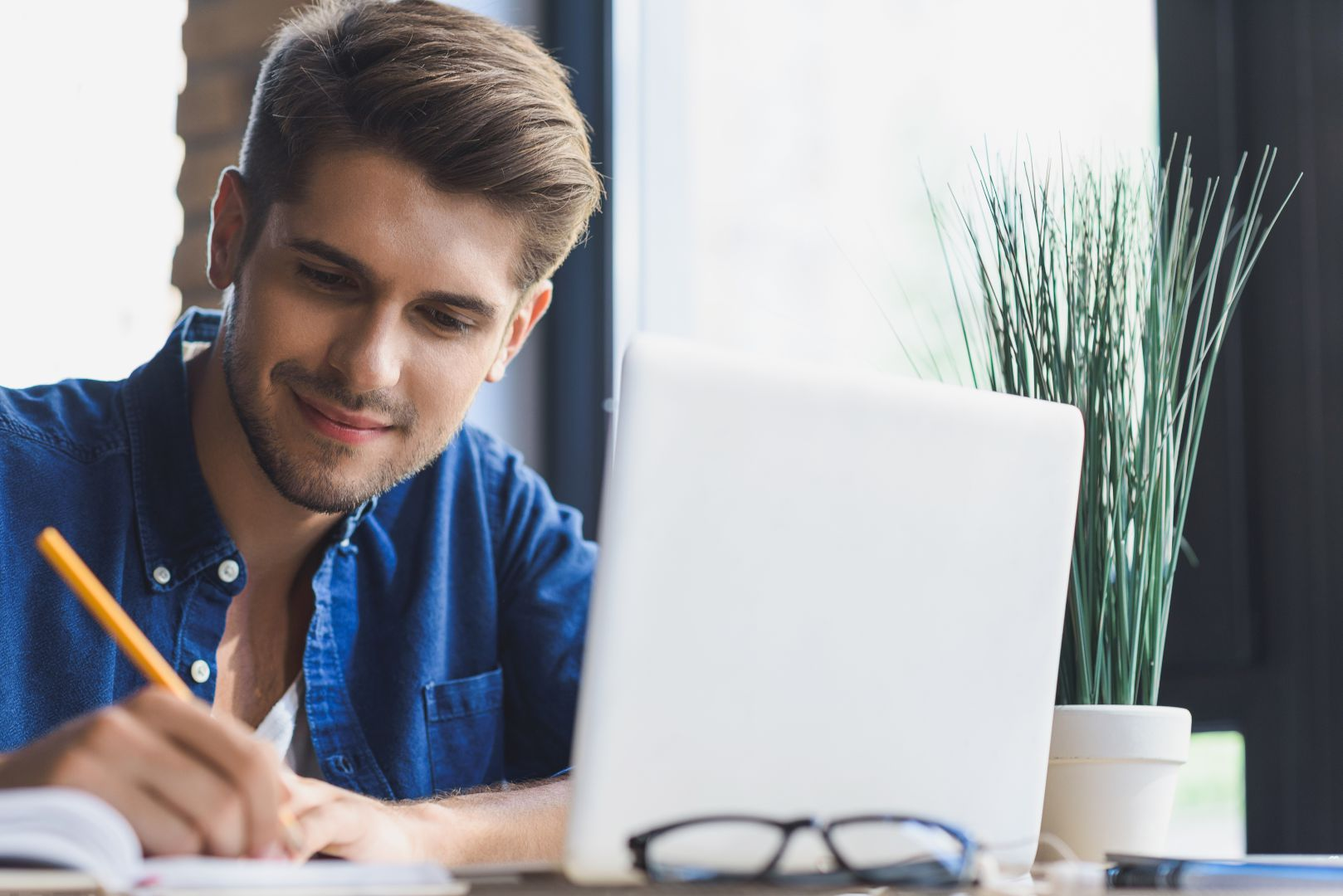Homme devant son ordinateur prenant des notes